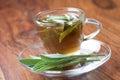 Sage tea with fresh sage inside teacup on wooden flooring