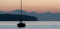 Sail boat calm waters sunrise cascade mountain range behind Stock Photo
