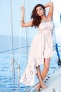 Sail boat model a beautiful young woman in a side high low white dress on a Stock Photo