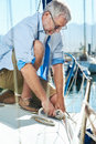 Sail boat yacht mooring portrait of senior man tying knot and securing a for his hobby Royalty Free Stock Photos