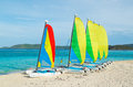 Sail boats on tropical beach with colorful sails catamarans Stock Photos