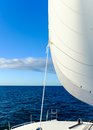 Sail full of wind on a yacht billowing out in the sailing across the wide blue ocean Royalty Free Stock Image