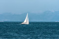 Sailboat floats quickly against the distant mountains a lone sails blue Royalty Free Stock Image