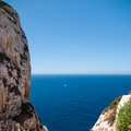 Sailboat on the horizon view from cliffs a yacht in blue sea Royalty Free Stock Image