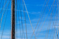 Sailboat mast and ropes in harbor against blue sky Royalty Free Stock Photo
