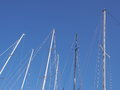Sailboat masts against the blue sky Royalty Free Stock Photo