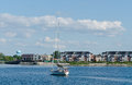 Sailboat motoring into the collingwood harbor boat and apartment buildingsin ontario Royalty Free Stock Images