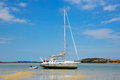 Sailboat parked in the sand at low tide. Royalty Free Stock Photo