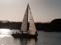 Sailboat returning to the marina at sunset crew preparing lower sails santa cruz harbor california Stock Photo