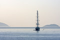 Sailboat in the sea at dawn sailing ship under bare poles with high masts on drift calm with a seagull and hills on horizon Royalty Free Stock Photo