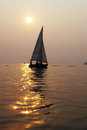 Sailboat in the setting sun drifting a calm Stock Images