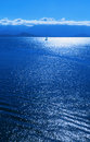 Sailboat on a shimmering blue ocean Stock Images