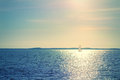 Sailboat in sunlight small on the sea Stock Photos