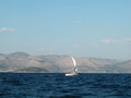 Sailboat surfing white mediterranean sea in croatia coast and mountains in background Stock Photos