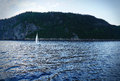 Sailboat on water in blue small a fjord dramatic cold and vignetting rendering Stock Image