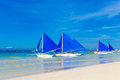 Sailboats with blue sails on a tropical beach. Journey and summer Royalty Free Stock Photo