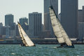 Sailboats racing in san francisco bay february two side by side front of the tall city buildings on a sunny day Stock Photo