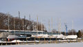 Sailboats winterized dry dock a row of sits in along the side of a building at a frozen marina Stock Photos