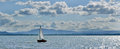 Sailing boat on the lake with clouded blue sky Stock Photo