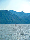 Sailing boat on a mountain lake little in the middle of with mountains in the background photo taken in summer morning lago d idro Royalty Free Stock Photography
