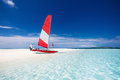 Sailing boat with red sail on a beach of deserted tropical islan island shallow blue water Stock Image