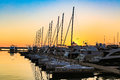 Sailing boats and luxury yachts docked in sea port in sea at sunset.