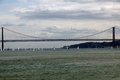 Sailing boats on river tejo in lisbon this magnificent bridge frames the many beneath it Royalty Free Stock Images