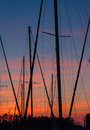 Sailing masts at sunset of harbored sailboats against colorful sky or sunrise Stock Photo