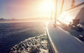 Sailing ocean boat on on water at sunrise with flare and outdoor lifestyle Royalty Free Stock Image