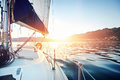 Sailing ocean boat yacht on on water at sunrise with flare and outdoor lifestyle Royalty Free Stock Photo