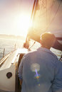 Sailing sunrise man with flare and boat on ocean Stock Photography