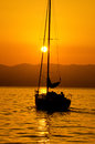 Sailing on sunset boat in orange colors of warm summer end of the day ocean quiet vacation Stock Images