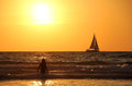 Sailing in sunset a girl going the sea while a boat is cruising the horizon at time taken at tel aviv israel Royalty Free Stock Photos