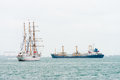 Sailing vessel and modern oil tanker ship on the sea near a port Royalty Free Stock Photography