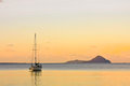 Sailing yacht on calm sea at sunset Stock Photos