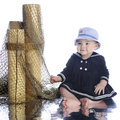 Sailor girl with fishnet an adorable barefoot baby sitting on a watery reflection while happily pulling on a on a white background Stock Photo