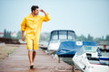 Sailor man in yellow cloak walking at the sea pier Royalty Free Stock Photo