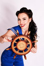 Sailor pin up girl with steering wheel on grey background Stock Photos
