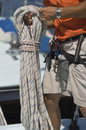 Sailor tying ropes on sailboat midsection of young Stock Photography