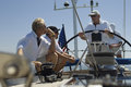 Sailors talking at the helm on a yacht against clear blue sky Stock Photography