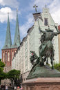 Saint george and the dragon berlin a sculpture of killing with his spear riding a horse facade of nikolaikirche with its twin Royalty Free Stock Image