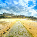 Saint malo beach and stone pathway low tide brittany france during europe Royalty Free Stock Images