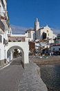 Saint mary church cadaques spain clear blue sky day in with of santa maria in the background and famous arches in foreground Royalty Free Stock Images