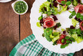 Salad with baked beet, blue cheese, ham and green mix with pesto. Royalty Free Stock Photo