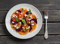 Salad with beets, oranges and soft cheese on a white plate Royalty Free Stock Photo