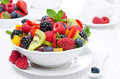 Salad of fresh fruit and berries in a bowl white cup tea the background horizontal closeup Stock Photography