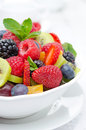 Salad of fresh fruit and berries in a white bowl cup tea the background closeup vertical Royalty Free Stock Photos