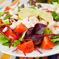 Salad with fresh vegetables and king prawns tomatoes beetroots decorated slices of lemon presented on a white plate Stock Photo