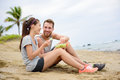 Salad healthy fitness couple eating food women and men laughing lunch sitting on beach after workout mixed race asian caucasian Stock Image