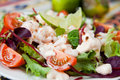 Salad with king prawns fresh vegetables tomatoes beetroots decorated slices of lemon presented on a white plate Stock Photo